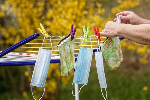 Hands hanging reusable cloth face masks outside to air dry