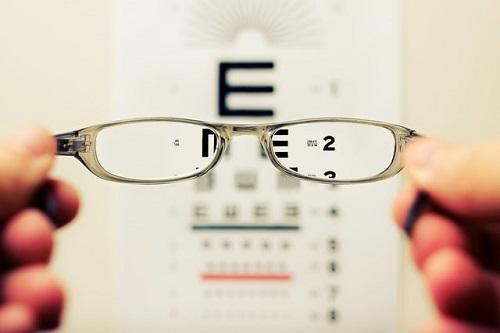 Glasses held up to eye exam chart