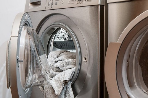 Open washing machine with towel hanging out