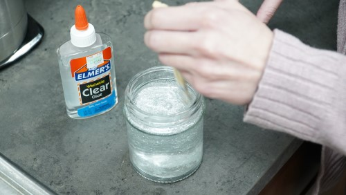 Stirring glue and water in the jar