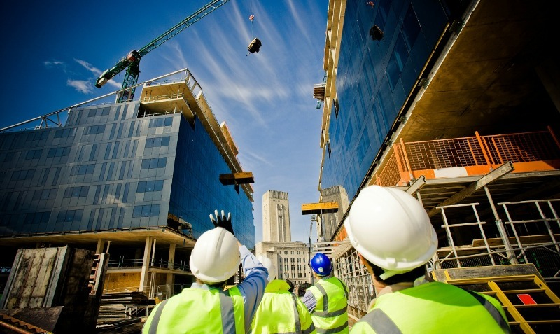 builders with hard hats in construction industry