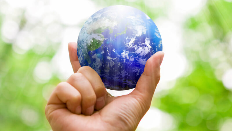 image of person holding earth in their fingers