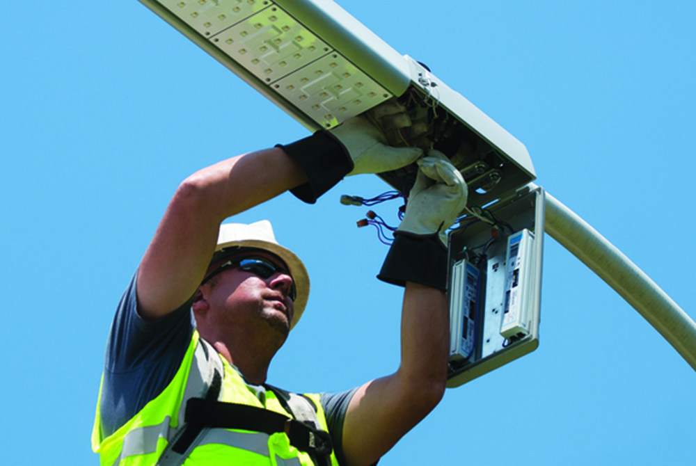 man installing LED shoebox retrofit kit in street lamp