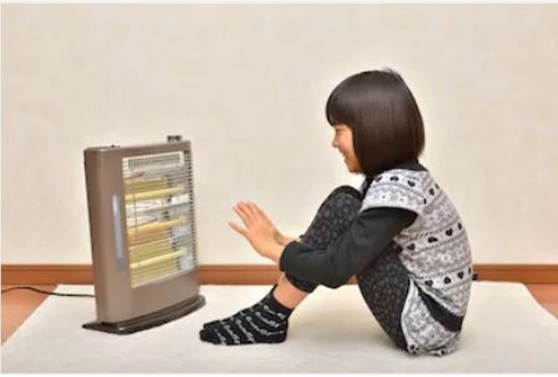 Girl warming up to space heater