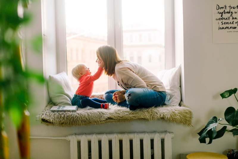 Mom and baby sitting above a heater on a ledge