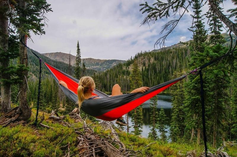 Girl laying in eno hammock staring at waterfall