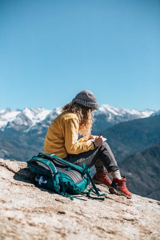 Girl journaling on mountain