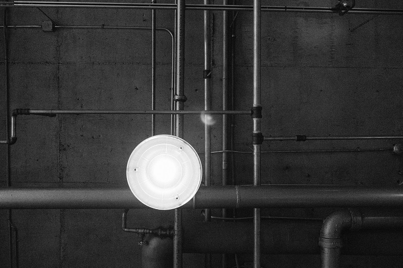 black and white image of a round high bay light on a ceiling
