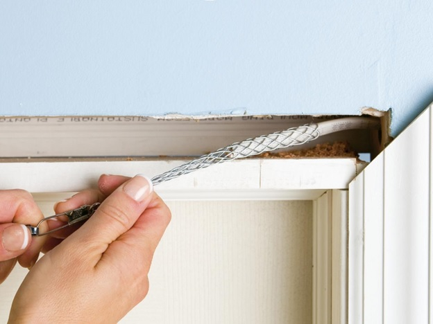 person pulling wire along interior of door jam with wire grip tool